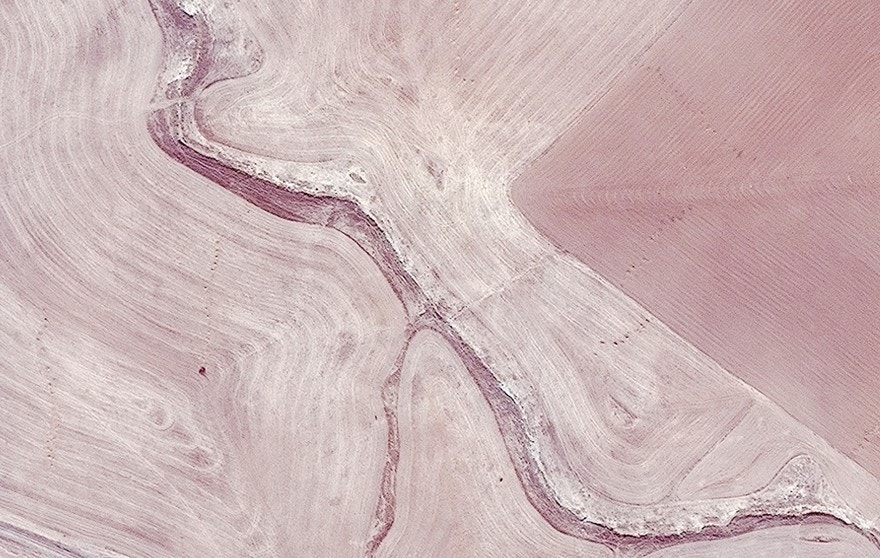 This combination of two satellite images provided by Allsource Analysis shows a suspected mass grave site next to a ravine at Badoush Prison in Mosul, Iraq, on Nov. 13, 2015, left, and the site on July 17, 2014, right. An analysis by The Associated Press has found 72 mass graves left behind by Islamic State extremists in Iraq and Syria, and many more are expected to be discovered as the group loses territory. (Allsource Analysis via AP)