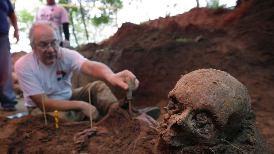 FILE - In this March 19, 2013 file photo, Rogelio Goiburu, member of Paraguay's Truth and Justice Commission, looks at skeletal remains found buried at the National Police Special Forces headquarters in Asuncion, Paraguay.  Paraguayan human rights groups said Tuesday, Aug. 30, 2016, they've identified the remains of an Italian woman and a Paraguayan man who were seized by authorities during a bloody regional crackdown on dissidents in the 1970s. The remains of both were found at the National Police Special Forces headquarters. (AP Photo/Jorge Saenz, File)