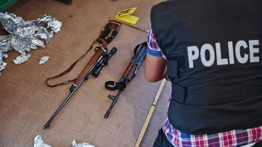 This Aug. 30, 2016, photo provided by Kosovo Police shows police officers seizing fire arms and bullets during a raid were Kosovo police have detained six people over their involvement with an attack with an explosive device at the parliament building earlier this month. The Aug. 4 attack damaged the buildings exterior but no one was injured. The local media have identified the suspects as members or supporters of the VETEVENDOSJE opposition party that is opposed to planed border demarcation deal with Montenegro. ( Kosovo Police via AP)