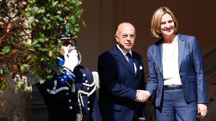 French Interior Minister Bernard Cazeneuve, center, welcomes Britain's Home Secretary Tuesday Aug. 30, 2016 in Paris. Tempers are rising among migrants squeezed in record numbers into a shrinking slum camp in France's port city of Calais, where hours-long waiting lines for food and showers and the tightening grip of security forces are leaving emotions raw. (AP Photo/Francois Mori)