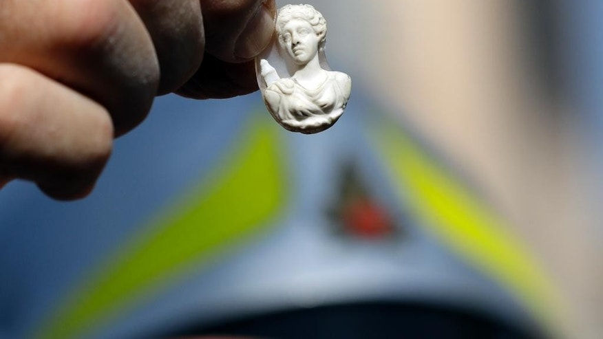 Father Savino D'Amelio, parish of the church of St. Augustine in Amatrice, central Italy, holds an icon of the Virgin Mary after retrieving it from the church, Tuesday, Aug. 30, 2016. Construction crews worked through the night to build a tent complex to host an Italian state funeral Tuesday in quake-devastated Amatrice after outraged residents rejected the government's plan to hold the service in a distant airport hangar. (AP Photo/Andrew Medichini)