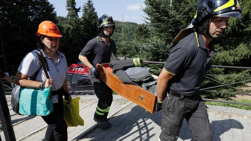 Firefighters recover residents' personal belongings, in Amatrice, central Italy, Tuesday, Aug. 30, 2016. Construction crews worked through the night to build a tent complex to host an Italian state funeral Tuesday in quake-devastated Amatrice after outraged residents rejected the government's plan to hold the service in a distant airport hangar. (AP Photo/Andrew Medichini)