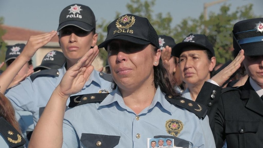 FILE - In this July 17, 2016 file photo, female police officers attend a funeral ceremony for colleagues killed during a failed military coup, in Ankara, Turkey. Turkey's official gazette says female police officers will be able to wear headscarves as part of their uniform. The ruling published over the weekend, Aug. 27-28, 2016, says the policewomen can wear headscarves under their caps or berets on condition they be the same color as the uniform and without a pattern.(AP Photo/Burhan Ozbilici, File)