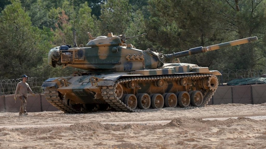 A Turkish tank stationed near the Syrian border, in Karkamis, Turkey, Monday, Aug. 29, 2016. Turkey's state-run news agency says three rockets fired from Syria have hit Turkish border town of Kilis, injuring five children, Turkish President Recep Tayyip Erdogan says Turkey will press ahead with its military operations in Syria until the Islamic State group and Kurdish militants no longer pose a security threat. Erdogan said Turkey was determined to take all steps necessary both inside Turkey and abroad to protect Turkish citizens.(Ismail Coskun/IHA via AP)