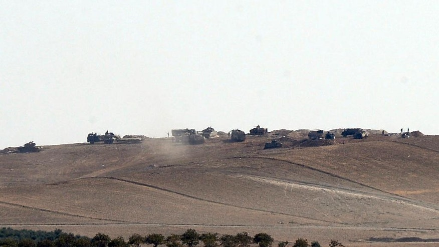 Turkish tanks and artillery are stationed near the Syrian border, in Karkamis, Turkey, Monday, Aug. 29, 2016. Turkey's state-run news agency says three rockets fired from Syria have hit Turkish border town of Kilis, injuring five children, Turkish President Recep Tayyip Erdogan says Turkey will press ahead with its military operations in Syria until the Islamic State group and Kurdish militants no longer pose a security threat. Erdogan said Turkey was determined to take all steps necessary both inside Turkey and abroad to protect Turkish citizens.(Ismail Coskun/IHA via AP)