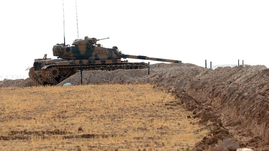 A Turkish tank is stationed near the Syrian border, in Karkamis, Turkey, Monday, Aug. 29, 2016. Turkey's state-run news agency says three rockets fired from Syria have hit Turkish border town of Kilis, injuring five children, Turkish President Recep Tayyip Erdogan says Turkey will press ahead with its military operations in Syria until the Islamic State group and Kurdish militants no longer pose a security threat. Erdogan said Turkey was determined to take all steps necessary both inside Turkey and abroad to protect Turkish citizens.(Ismail Coskun/IHA via AP)