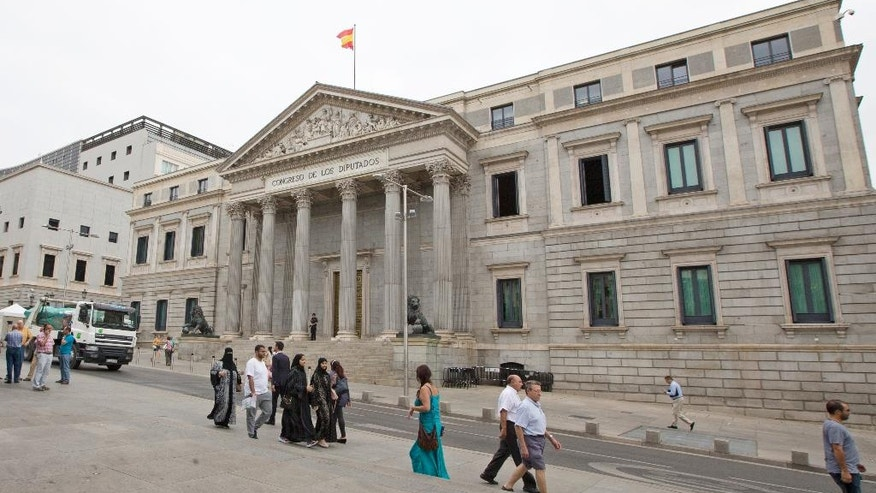 People walk past the Spanish Parliament in Madrid, Spain, Tuesday, Aug. 30, 2016. Spain's acting Premier Mariano Rajoy is to start a two-day parliamentary debate later Tuesday ahead of a vote on his bid to form a minority government and end an eight-month political impasse, but the signs are he won't be successful. If he fails, he has another chance Friday when he only needs more votes in favor than against, but nothing indicates he can win that either. (AP Photo/Paul White)