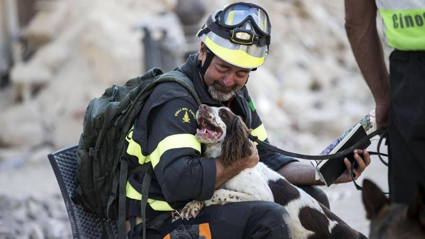 A firefighter cuddles his dog as rescuers continue searching through the rubble in Amatrice, central Italy, Monday, Aug. 29, 2016 after last Wednesday's earthquake. (Massimo Percossi/ANSA via AP)