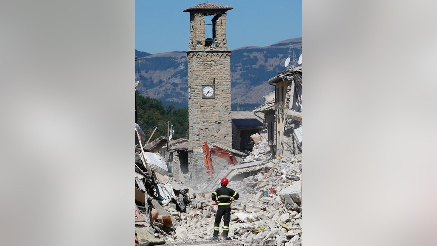 A firefighter stands amid rubble as he watches the bell tower of Amatrice, central Italy, Monday, Aug. 29, 2016. Italian authorities are pondering how to provide warmer, less temporary housing for quake homeless living in tents in the Apennine Mountains region. Nearly 2,700 people whose homes collapsed or left unsafe by the Aug. 24 temblor now stay in 58 tent camps or other shelters arranged by the Civil Protection agency. (AP Photo/Antonio Calanni)