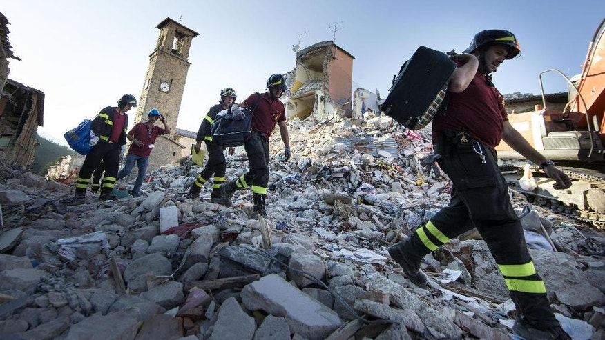 Firefighters carry personal belongings retrieved from houses, in Amatrice, central Italy, Monday, Aug. 29, 2016 after last Wednesday's earthquake. With thousands left homeless after Wednesday's earthquake, authorities are debating how to provide warmer, sturdier housing for them besides the rows of emergency blue tents set up in the Apennine Mountains, where even summer nights can get chilly. (Massimo Percossi/ANSA via AP)