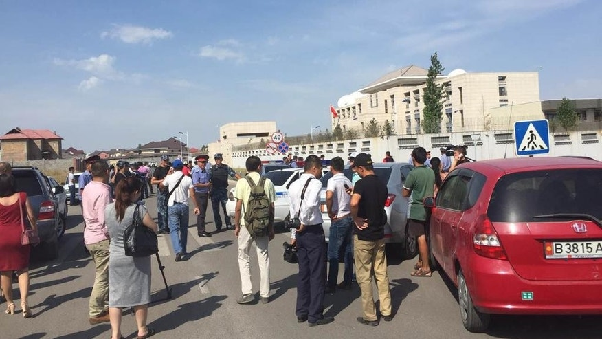 In this photo released by China's Xinhua News Agency, people gather near the site of an explosion in Bishkek, Kyrgyzstan, Tuesday, Aug. 30, 2016. Kyrgyzstan's deputy prime minister says a suicide bomber has rammed his car into the gate of the Chinese embassy compound in the capital Bishkek, detonating a bomb and injuring three embassy employees. (Chen Yao/Xinhua via AP)