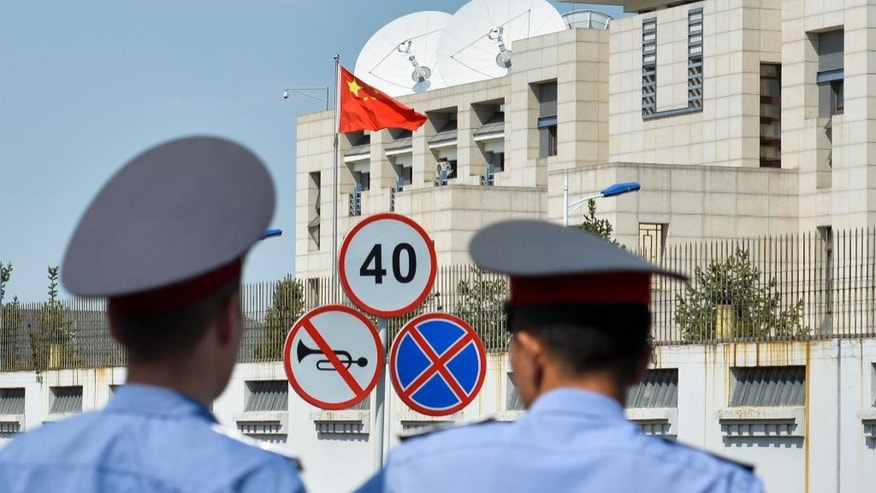 Kyrgyz police officers look at the Chinese Embassy in Bishkek, Kyrgyzstan, Tuesday, Aug. 30, 2016. A suspected suicide bomber on Tuesday crashed a car through the entrance of the Chinese Embassy in the Kyrgyzstan capital of Bishkek, detonating a bomb that killed the attacker and wounded embassy employees. (AP Photo/ Vladimir Voronin)