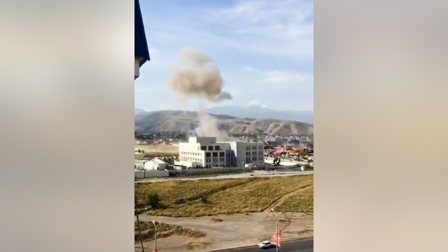 In this image made from a video provided by the Kloop Media Foundation, smoke rises above the Chinese Embassy in Bishkek, Kyrgyzstan, Tuesday, Aug. 30, 2016. A suspected suicide bomber on Tuesday crashed a car through the entrance of the Chinese Embassy in the Kyrgyzstan capital of Bishkek, detonating a bomb that killed the attacker and wounded embassy employees. (Kloop Media Foundation photo via AP)