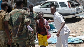 Somali soldiers help a man, center, who was wounded by a blast near the presidential palace in the capital Mogadishu, Somalia, Tuesday, Aug. 30, 2016. A suicide bomber has detonated an explosives-laden truck near the gate of Somalia's presidential palace in the capital on Tuesday, killing at least five people, police say. (AP Photo/Farah Abdi Warsameh)