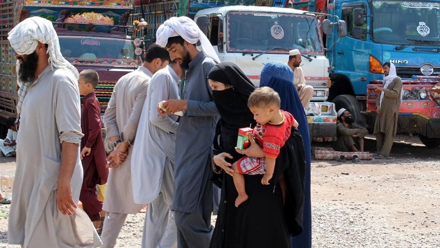 In this Aug. 18, 2016 photo, an Afghan refugee family who fled their country, arrive to the UNHCR terminal en route to Afghanistan, in Peshawar, Pakistan. Since the death of Taliban leader Mullah Mansour, Pakistan's Interior Ministry has launched a stepped-up campaign to verify the identity of roughly 1.5 million Afghans living in Pakistan, many possessing Pakistani identity cards, some legally obtained and others illegally acquired. Mansour was carrying a Pakistani passport and identity card under an alias. (AP Photo/Mohammad Sajjad)