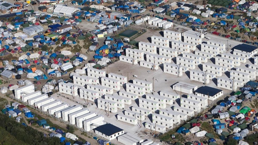 FILE - This Aug. 24, 2016 file photo shows an aerial view of the migrant camp in Calais, northern France. Tempers are rising among migrants squeezed in record numbers into a shrinking slum camp in France's port city of Calais, where hours-long waiting lines for food and showers and the tightening grip of security forces are leaving emotions raw. (AP Photo/Michel Spingler, File)