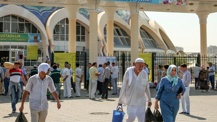 People walk at a central market in Tashkent, Uzbekistan, Tuesday, Aug. 30, 2016. News agencies report a concert marking Uzbekistan's 25th anniversary of independence from the Soviet Union has been cancelled amid uncertainty about the health of the country's hospitalized president. A poster in the back reads 'Beautiful and unique, sacred Motherland, I can sacrifice my life to my Uzbekistan.' (AP Photo)