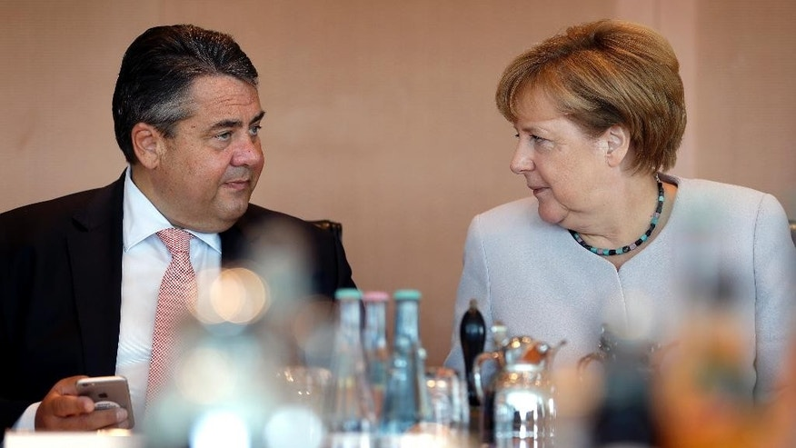 Germany's Chancellor Angela Merkel, right, and Vice-Chancellor Sigmar Gabriel talk prior to the weekly cabinet meeting at the Chancellery in Berlin, Germany, Wednesday, Aug. 31, 2016. (AP Photo/Michael Sohn)