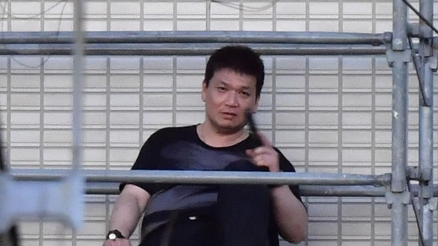 Yasuhide Mizobata, a murder suspect, holding guns sits on scaffoldings as he holes up at an apartment in a standoff after he fired at a police car and escaped, in Wakayama, central Japan, Wednesday, Aug. 31, 2016. Wakayama police said Wednesday that Mizobata, 45, is wanted as prime suspect in a shooting Monday at a small construction company, where he allegedly shot one employee dead and left three others injured. (Ren Onuma/Kyodo News via AP)