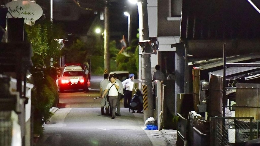 Plainclothes police walk around an area where Yasuhide Mizobata, a murder suspect, was found in Wakayama, central Japan, Wednesday, Aug. 31, 2016. Mizobata, a suspect in a fatal shooting, holes up at an apartment in an armed standoff after he fired at a police car and escaped. (Ren Onuma/Kyodo News via AP)