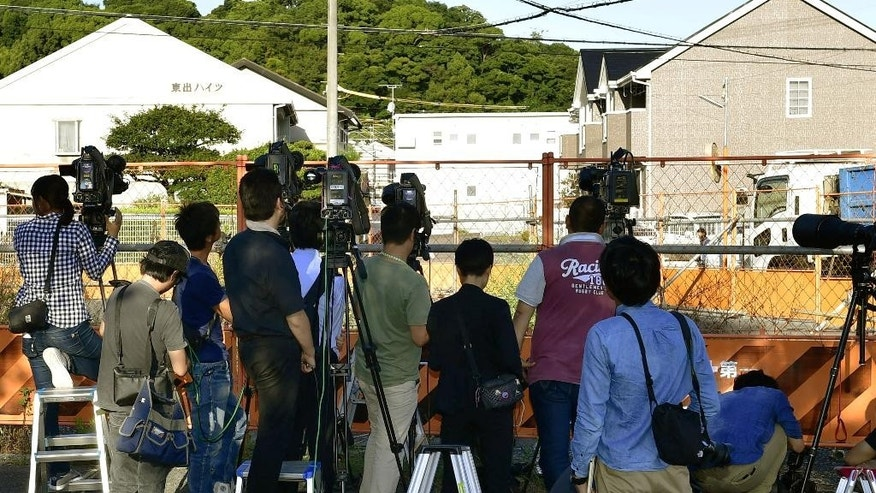 Journalists look at an apartment, center back, where Yasuhide Mizobata, a murder suspect, with guns holes up in a standoff after he fired at a police car and escaped, in Wakayama, central Japan, Wednesday, Aug. 31, 2016. Wakayama police said Wednesday that Mizobata is wanted as prime suspect in a shooting Monday at a small construction company, where he allegedly shot one employee dead and left three others injured. (Ren Onuma/Kyodo News via AP)