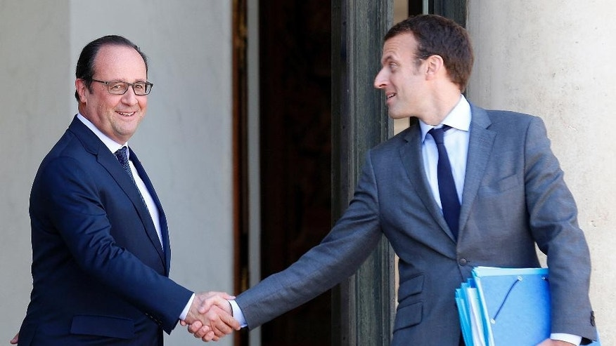 FILE - In this July 31, 2015 file photo, French President Francois Hollande, left, shake hands with the French Economy minister Emmanuel Macron in the lobby of the Elysee Palace. Macron, an outspoken former investment banker who has encouraged start-ups and more labor flexibility, has quit the socialist government Tuesday Aug. 30, 2016 amid speculation that he is considering a presidential bid. (AP Photo/Jacques Brinon, File)