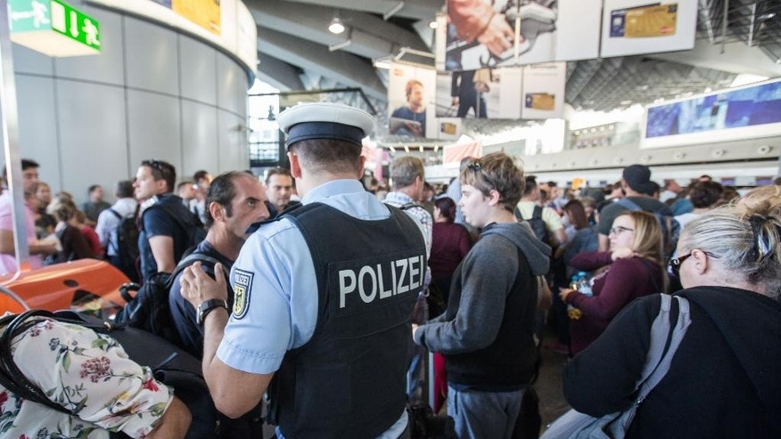 A policeman talks to people in the departure area at Frankfurt airport, central Germany, Wednesday, Aug31, 2016. Authorities say a portion of Frankfurt Airport's Terminal 1 has been evacuated after a person entered a secure area without undergoing required searches. (Frank Rumpenhorst/dpa via AP)