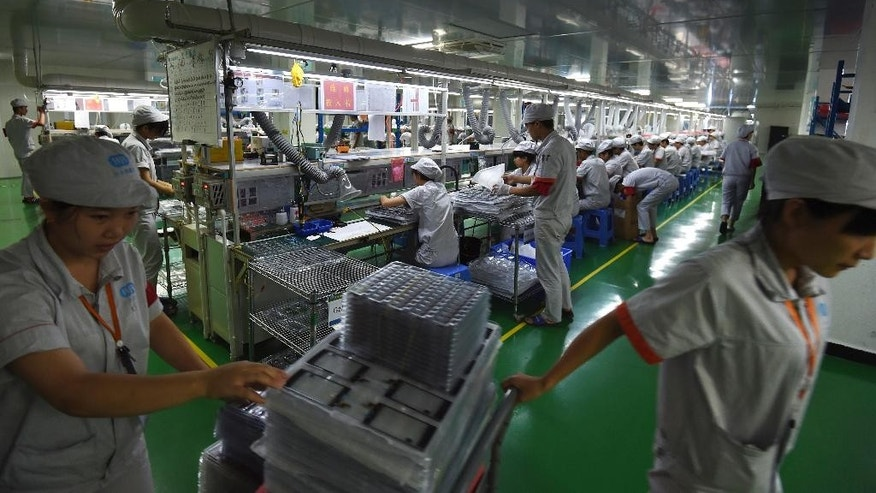 In this Aug. 13, 2016 photo, Chinese workers assemble smartphones on a production line at a factory in Guang'an, in southwest China's Sichuan province. Leaders of the United States, China and other Group of 20 major economies who meet on Sunday, Sept. 4, 2016 in Hangzhou, China, say more trade would help shore up sluggish global growth but are tightening their own controls on imports. (Chinatopix via AP)