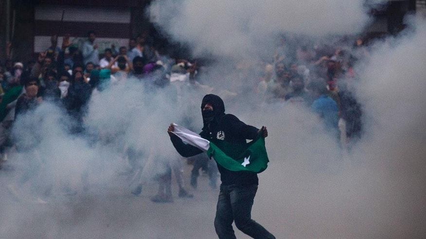A Kashmiri Muslim protester engulfed in teargas smoke holds Pakistani flag during a protest in Srinagar, Indian controlled Kashmir, Wednesday, Aug. 31, 2016. Protests against Indian rule erupted at many places in Kashmir on Wednesday after authorities lifted a curfew throughout the disputed Himalayan region for the first time in 54 days. A young man was killed and several others were injured in clashes between rock-throwing protesters and government forces.(AP Photo/Dar Yasin)