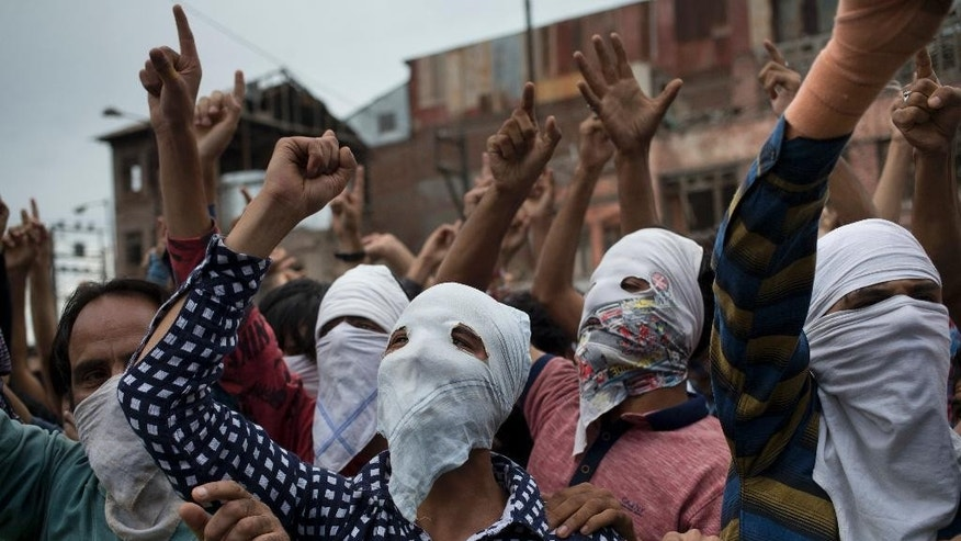 Masked Kashmiri Muslim protesters shout pro-freedom slogans during a protest march in Srinagar, Indian controlled Kashmir, Wednesday, Aug. 31, 2016. Protests against Indian rule erupted at many places in Kashmir on Wednesday after authorities lifted a curfew throughout the disputed Himalayan region for the first time in 54 days. A young man was killed and several others were injured in clashes between rock-throwing protesters and government forces. (AP Photo/Dar Yasin)
