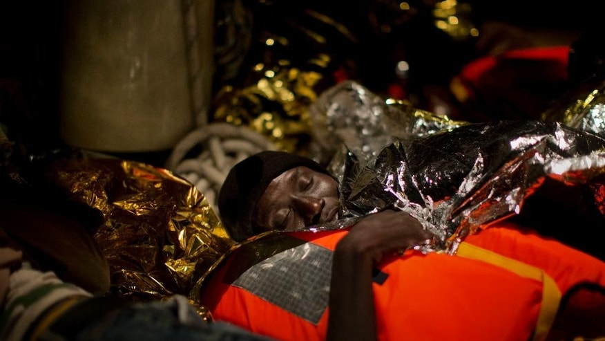 A refugee from Eritrea sleeps on the Astral vessel after being rescued from the Mediterranean sea, about 13 miles north of Sabratha, Libya, Monday, Aug. 29, 2016. Thousands of migrants and refugees were rescued Monday morning from more than 20 boats by members of Proactiva Open Arms NGO before transferring them to the Italian cost guards and others NGO vessels operating at the zone. (AP Photo/Emilio Morenatti)
