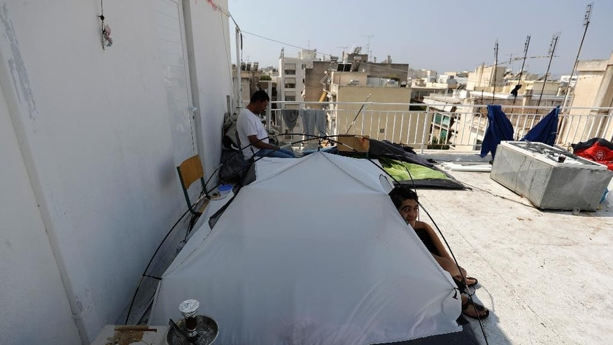 Abdulsalam Mahmoud from Syria, 18, sits at his tent on the terrace of an abandoned hospital wing, which is used as a makeshift shelter for about 150 Syrian refugees in Athens, Wednesday, Aug. 31, 2016. Over 59,000 people remain stranded in the country, most in army-built camps on the mainland and about 7,800 refugees are receiving hotel vouchers or live in vacant apartments. (AP Photo/Thanassis Stavrakis)
