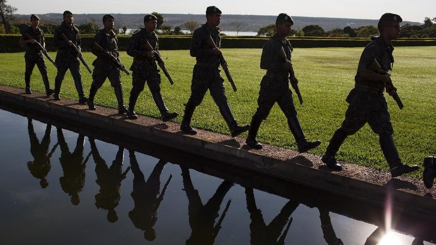 Soldiers march in the garden of the official presidential residence Alvorada Palace,  in Brasilia, Brazil, Wednesday, Aug. 31, 2016. Senators debated the fate of Brazilian President Dilma Rousseff into the wee hours of Wednesday ahead of a planned vote later in the day on whether to remove Rousseff permanently as leader of Latin America's most populous country. (AP Photo/Leo Correa)