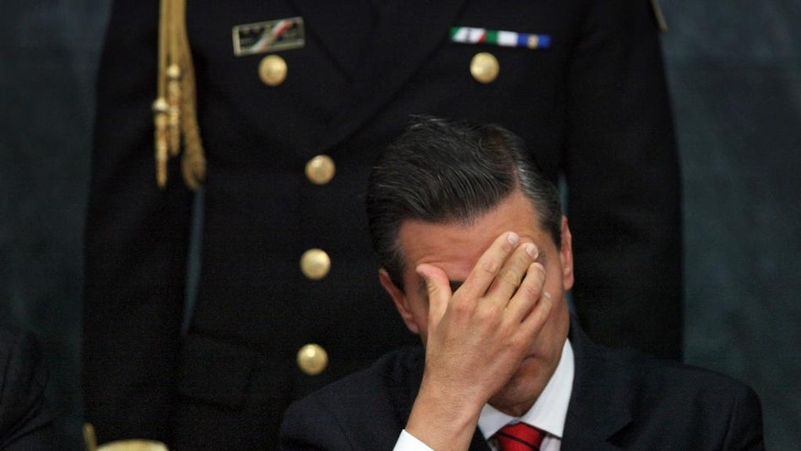 FILE - In this  Jan. 21, 2015, file photo, Mexico's President Enrique Pena Nieto listens in during an act to promote housing for lower income families, single mothers and members of the armed forces, at the Los Pinos presidential residence in Mexico City. As he prepares for his 2016 report to congress, Pena Nieto will reflect on a year that has seen rising homicide rates, a sluggish economy and a midterm electoral rout of his party. (AP Photo/Marco Ugarte, File)