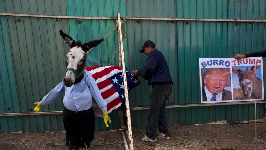 FILE - In this May 1, 2016, file photo, a man dresses a donkey to resemble Donald Trump in preparation for the costume competition at the annual donkey festival in Otumba, Mexico state, Mexico. In a surprise move, Donald Trump will travel to Mexico on Wednesday, Aug. 31, to meet with President Enrique Pena Nieto, just hours before the Republican delivers a highly anticipated speech on immigration. Pena Nieto has been sharply critical of Trump's original immigration policy and compared his language to that of dictators Adolf Hitler and Benito Mussolini, saying it had hurt U.S.-Mexico relations. (AP Photo/Rebecca Blackwell, File)