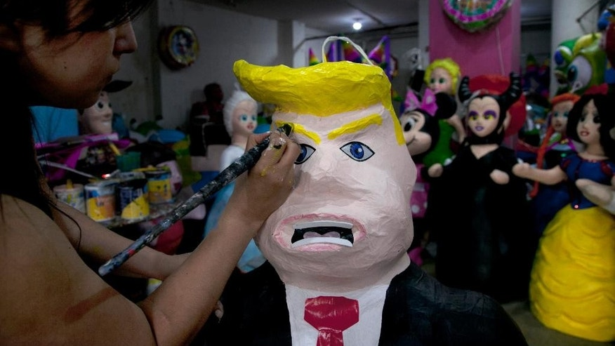 "FILE - In this Friday, July 10, 2015 file photo, Alicia Lopez Fernandez paints a pinata depicting Donald Trump at her family's store ""Pinatas Mena Banbolinos"" in Mexico City. In a surprise move, Donald Trump will travel to Mexico on Wednesday, Aug. 31, to meet with President Enrique Pena Nieto, just hours before the Republican delivers a highly anticipated speech on immigration. Pena Nieto has been sharply critical of Trump's original immigration policy and compared his language to that of dictators Adolf Hitler and Benito Mussolini, saying it had hurt U.S.-Mexico relations. (AP Photo/Marco Ugarte, File)"