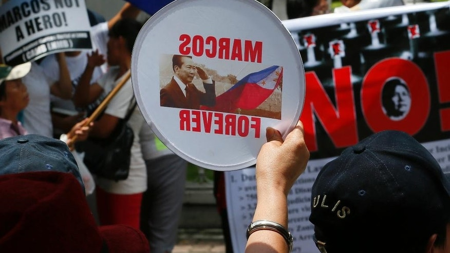 Pro-Marcos protesters, foreground, taunt anti-Marcos demonstrators as they picket the Philippine Supreme Court to coincide with the oral arguments following petitions filed by various groups opposing the burial of the late dictator Ferdinand Marcos at the Heroes Cemetery Wednesday, Aug. 31, 2016, in Manila, Philippines. Lawyers for victims of Philippine dictator Ferdinand Marcos's regime said Wednesday that the late leader was unfit for a hero's burial, as they argued at a hearing on petitions against President Rodrigo Duterte's directive to have Marcos buried at a heroes' cemetery. (AP Photo/Bullit Marquez)
