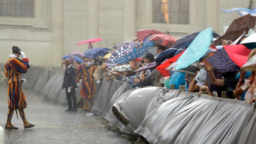 People try shelter from heavy rain during Pope Francis's general audience in St.Peter's Square, at the Vatican, Wednesday, Aug. 31, 2016. (AP Photo/Andrew Medichini)