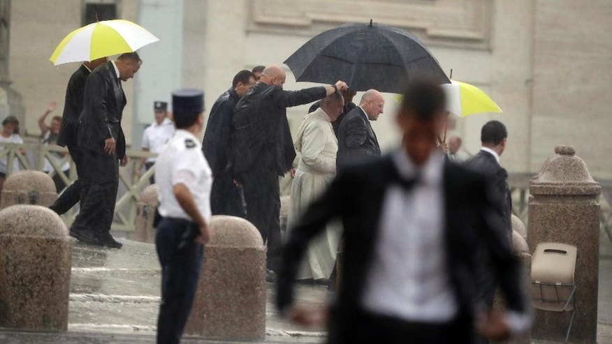 Pope Francis is escorted under an umbrella during a thunderstorm at the end of his general audience, in St.Peter's Square, at the Vatican, Wednesday, Aug. 31, 2016. The pontiff had to interrupt his final greetings and leave in a closed car as a sudden rain storm hit the Vatican. (AP Photo/Andrew Medichini)
