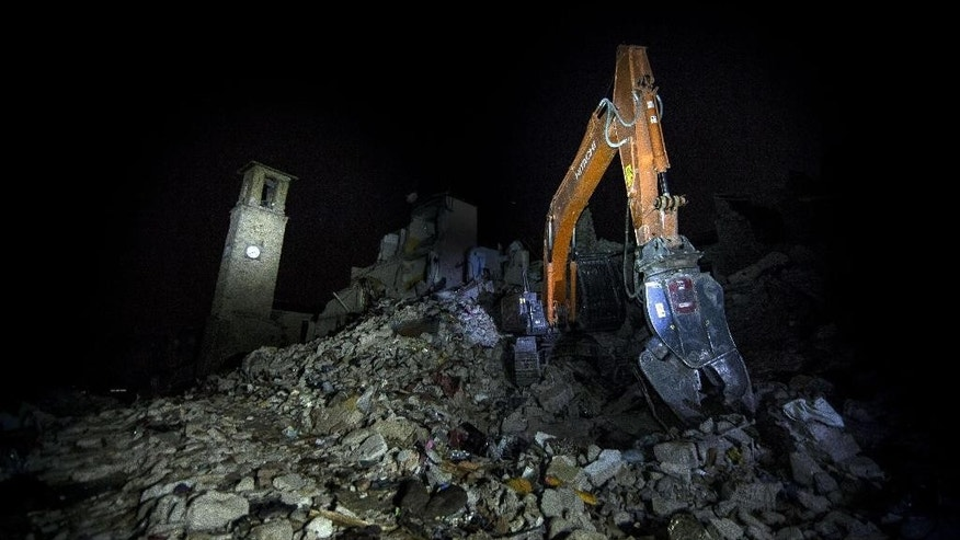 An excavator piles rubble as the bell tower of Amatrice stands in the background, in Amatrice, central Italy, at the same time, 3.36am, a week after a deadly quake, Wednesday, Aug. 31, 2016. A magnitude 6.2 earthquake struck central Italy last Wednesday, causing several hundred deaths and flattened three towns in central Italy. (Massimo Percossi/ANSA via AP)