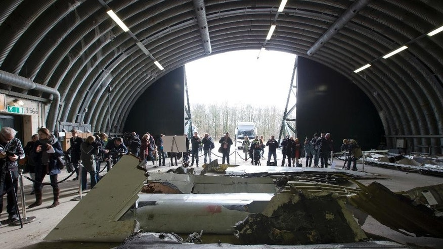 FILE- In this Tuesday, March 3, 2015 file photo, journalists take images of parts of the wreckage of the Malaysia Airlines Flight 17 displayed in a hangar at Gilze-Rijen airbase, Netherlands. In an open letter Wednesday, Aug. 31, 2016, frustrated relatives of those killed when Malaysia Airlines Flight 17 was shot out of the sky over eastern Ukraine say they are appealing to the European Union's top diplomat to put pressure on Russia, Ukraine and the United States to hand over intelligence and radar data to investigators. (AP Photo/Peter Dejong, File)