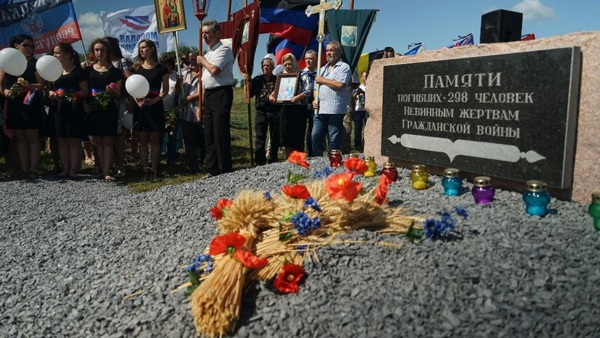 FILE- In this Friday, July 17, 2015 file photo, people stand with Orthodox crosses and icons as they attend a memorial service at the crash site of the Malaysia Airlines Flight 17, near the village of Hrabove, eastern Ukraine. In an open letter Wednesday, Aug. 31, 2016, frustrated relatives of those killed when Malaysia Airlines Flight 17 was shot out of the sky over eastern Ukraine say they are appealing to the European Union's top diplomat to put pressure on Russia, Ukraine and the United States to hand over intelligence and radar data to investigators. (AP Photo/Mstyslav Chernov, File)
