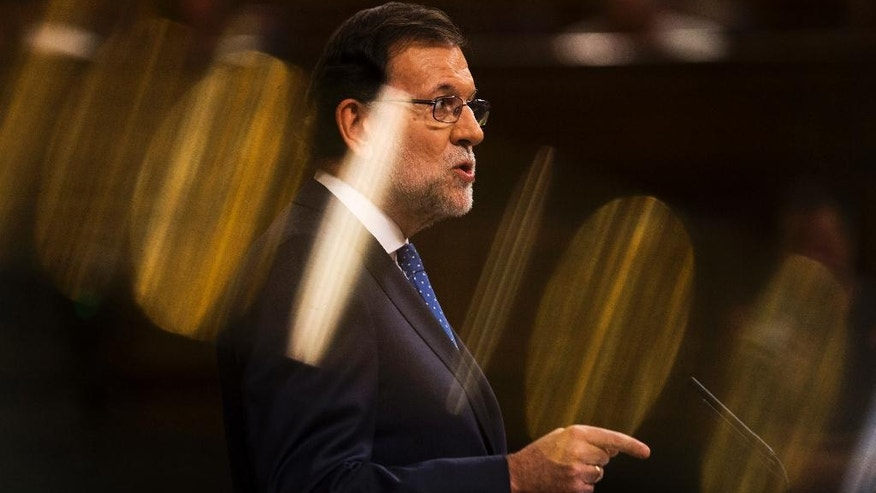 Spain's acting Prime Minister and Popular Party leader Mariano Rajoy addresses lawmakers during the first of the two day investiture debate at the Spanish parliament in Madrid, Tuesday, Aug. 30, 2016. Rajoy is to start a two-day parliamentary debate later Tuesday ahead of a vote on his bid to form a minority government and end an eight-month political impasse, but the signs are he won't be successful. If he fails, he has another chance Friday when he only needs more votes in favor than against, but nothing indicates he can win that either. The yellow lights come from the glare of a metal bar.  (AP Photo/Francisco Seco)