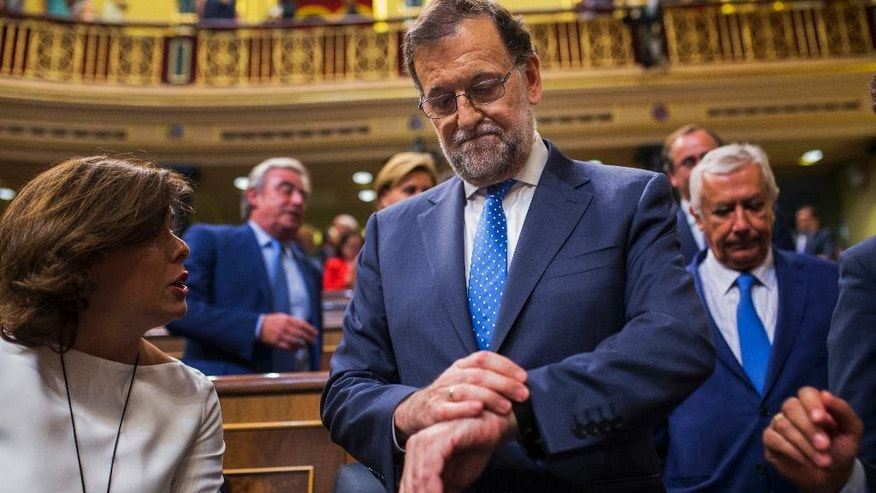 Spain's acting Prime Minister and Popular Party leader Mariano Rajoy looks at his watch at the end of the first of the two-day investiture debate at the Spanish parliament in Madrid, Tuesday, Aug. 30, 2016. Rajoy started a two-day parliamentary debate later Tuesday ahead of a vote on his bid to form a minority government and end an eight-month political impasse, but the signs are he won't be successful. (AP Photo/Francisco Seco)