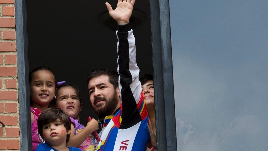 FILE - In this Aug. 12, 2015, file photo, Daniel Ceballos, former mayor of the western city of San Cristobal, waves to supporters and members of the press from an apartment window with his daughters, Maria Veronica, left, Maria Daniel, second from left, son Juan Daniel and wife Patricia de Ceballos in Caracas, Venezuela. With a Thursday, Sept. 1, 2016, march called to pressure electoral authorities to allow a recall referendum against President Nicolas Maduro, authorities have moved Ceballos from house arrest back to prison while he awaits trial on civil rebellion charges stemming from the 2014 protests. Authorities said he was plotting to flee and carry out violence during the protests. (AP Photo/Ariana Cubillos, File)