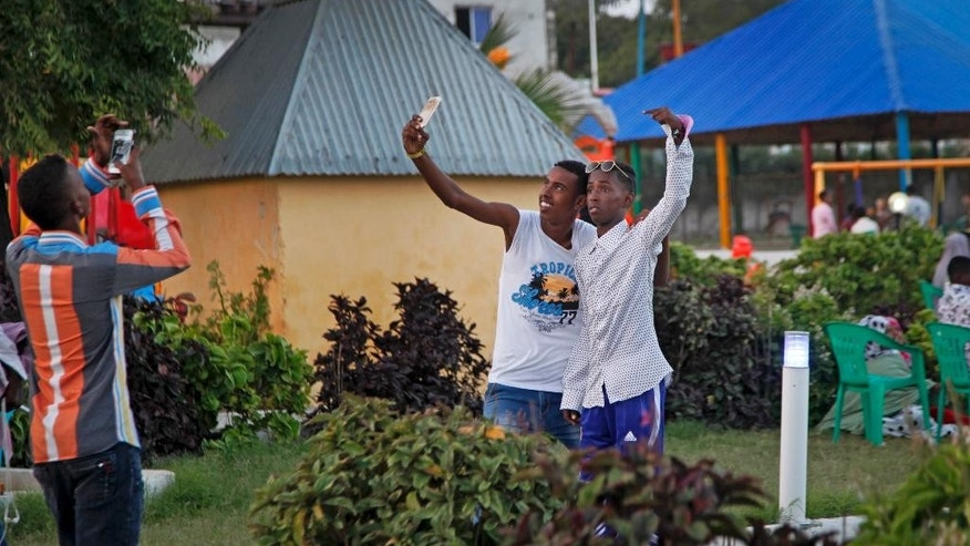 In this photo taken Sunday, Aug. 21, 2016, young Somali men take selfies in the Peace Garden public park in Mogadishu, Somalia. War-weary Somalis are trying to relax and rebuild their country after decades of violence, but the homegrown Islamic extremists al-Shabab keep striking at the heart of its seaside capital, killing scores of people so far this year. (AP Photo/Farah Abdi Warsameh)