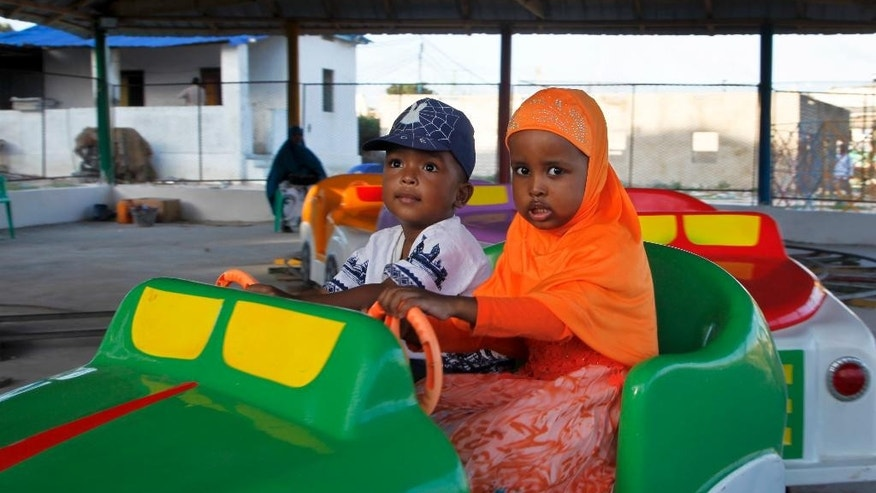In this photo taken Sunday, Aug. 21, 2016, Somali children play on a ride at the Peace Garden public park in Mogadishu, Somalia. War-weary Somalis are trying to relax and rebuild their country after decades of violence, but the homegrown Islamic extremists al-Shabab keep striking at the heart of its seaside capital, killing scores of people so far this year. (AP Photo/Farah Abdi Warsameh)