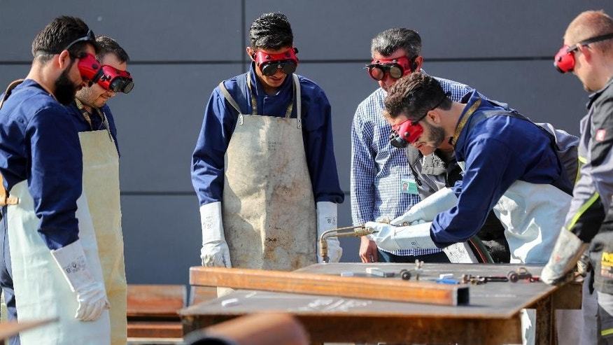 Syrian refugees learning how to reconstruct houses at the education center of the pioneer troop of the German military in Ingolstadt, Germany, Thursday, Sept. 1, 2016. Germany's military is starting a pilot project to help Syrian refugees learn civil reconstruction skills, in hopes that they'll eventually be able to help rebuild their homeland. (Kay Nietfeld/dpa via AP)
