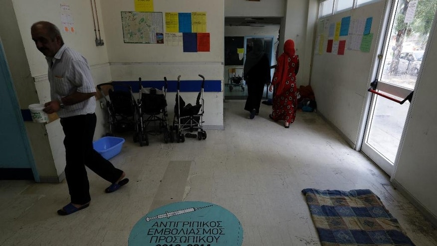 People walk in an abandoned hospital wing, which is used as a makeshift shelter for about 150 Syrian refugees in Athens, Wednesday, Aug. 31, 2016. Over 59,000 people remain stranded in the country, most in army-built camps on the mainland and about 7,800 refugees are receiving hotel vouchers or live in vacant apartments. The sign on the floor reads ''Staff flu shot 2010-2011.'' (AP Photo/Thanassis Stavrakis)