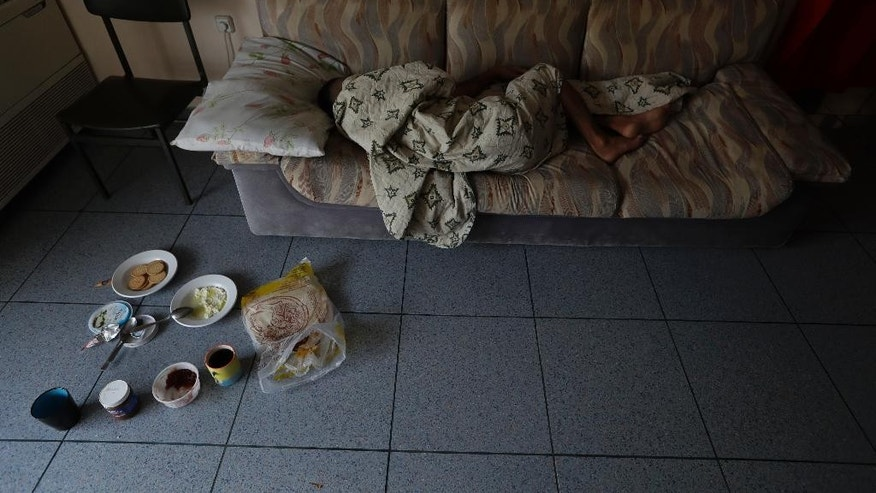 A man sleeps on a sofa at an abandoned hospital wing, which is used as a makeshift shelter for about 150 Syrian refugees in Athens, Wednesday, Aug. 31, 2016. Over 59,000 people remain stranded in the country, most in army-built camps on the mainland and about 7,800 refugees are receiving hotel vouchers or live in vacant apartments. (AP Photo/Thanassis Stavrakis)